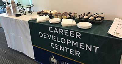 Table with coffee and pastries draped with Career Development Center banner