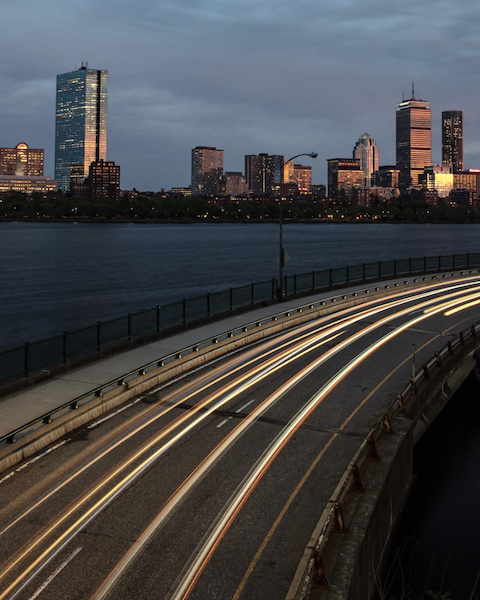 The Boston city skyline at dusk with fast-moving traffic