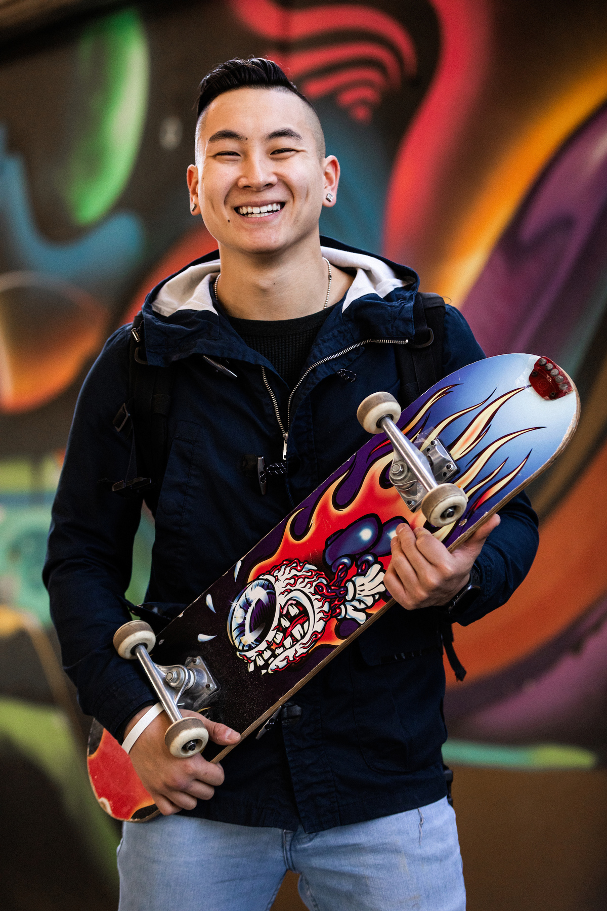 Dan Redznak holding a skateboard and smiling.