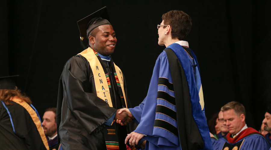Suffolk student Isaac Boateng shakes hands with Suffolk President Marisa Kelly at his commencement.