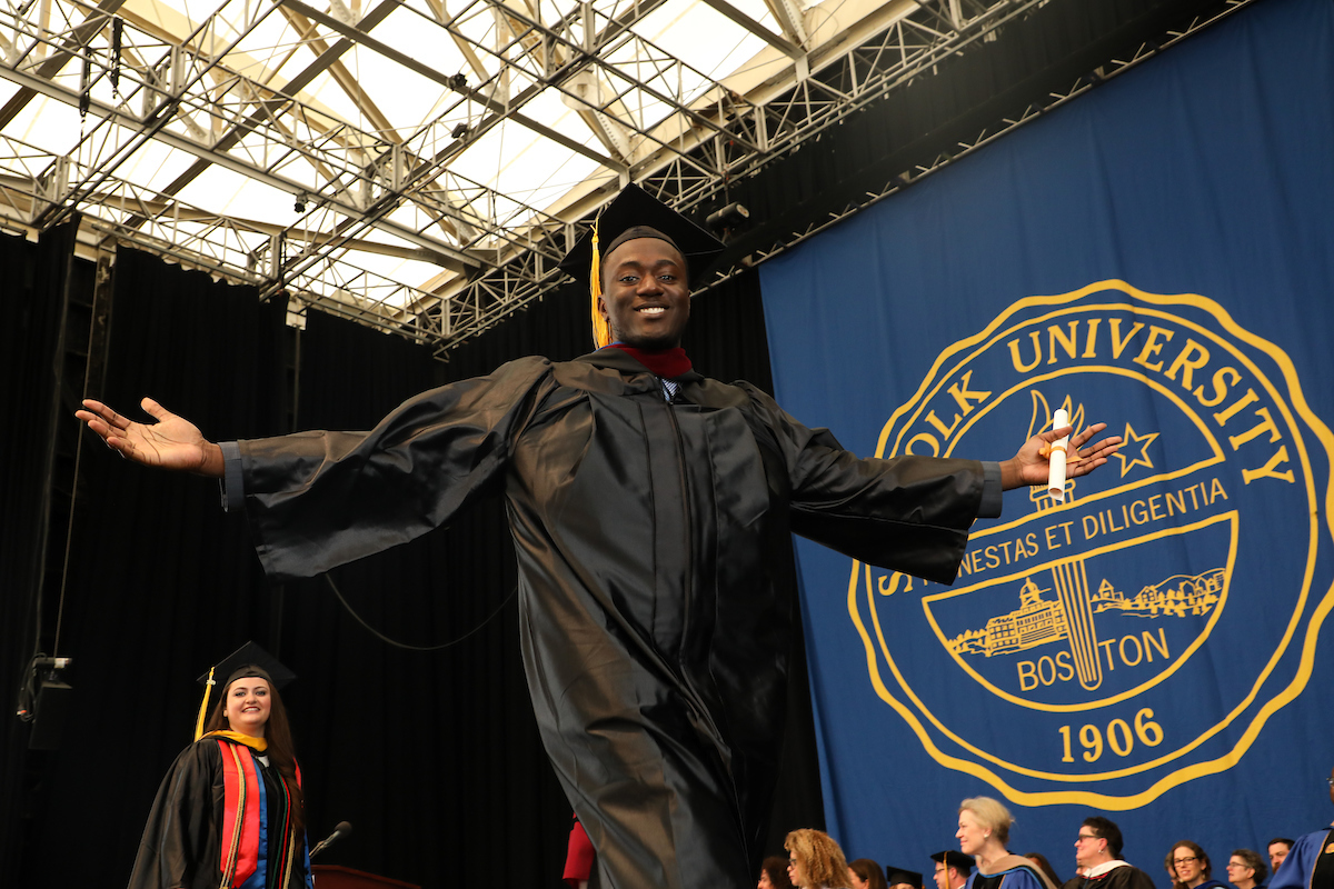 Clevis Murray crosses the stage at the Commencement ceremony with his arm spread wide.