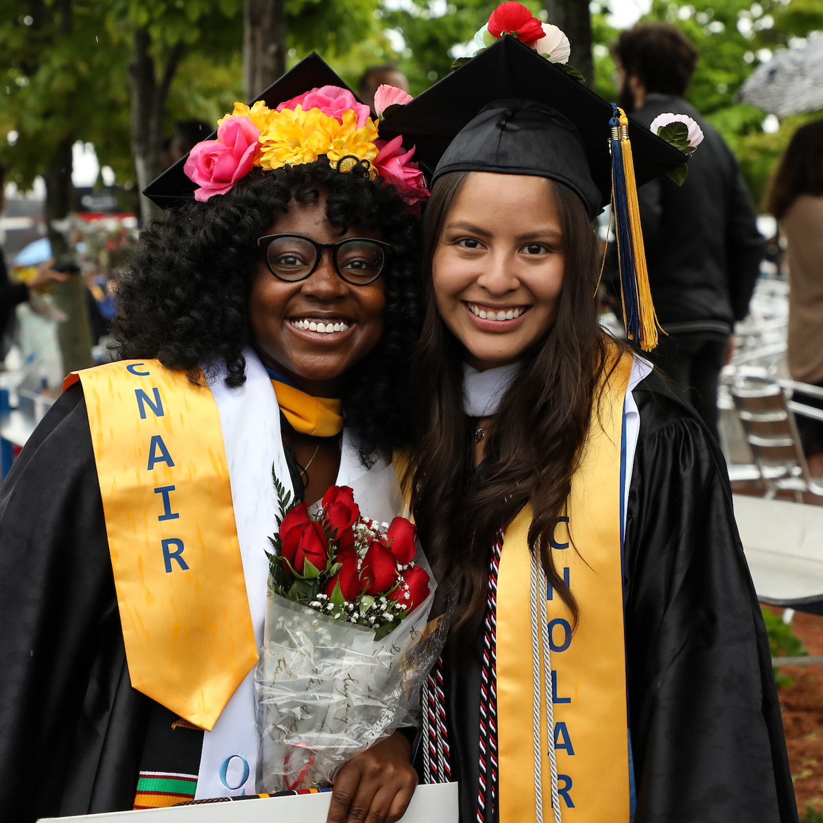 Arly posing for a photo with a friend wearing her cap and gown following Commencement.