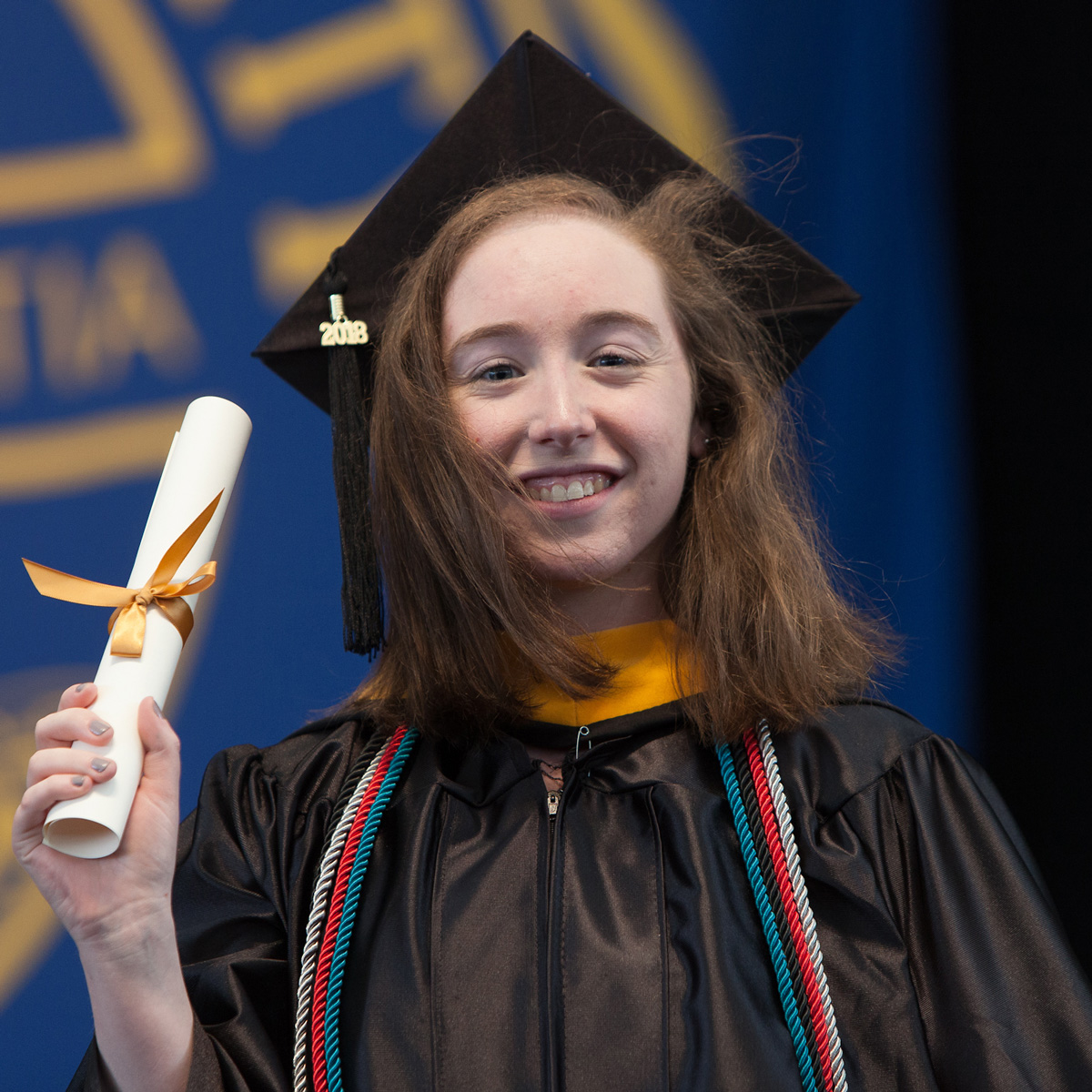 Ashley holding up her scroll while walking across the stage during Commencement.