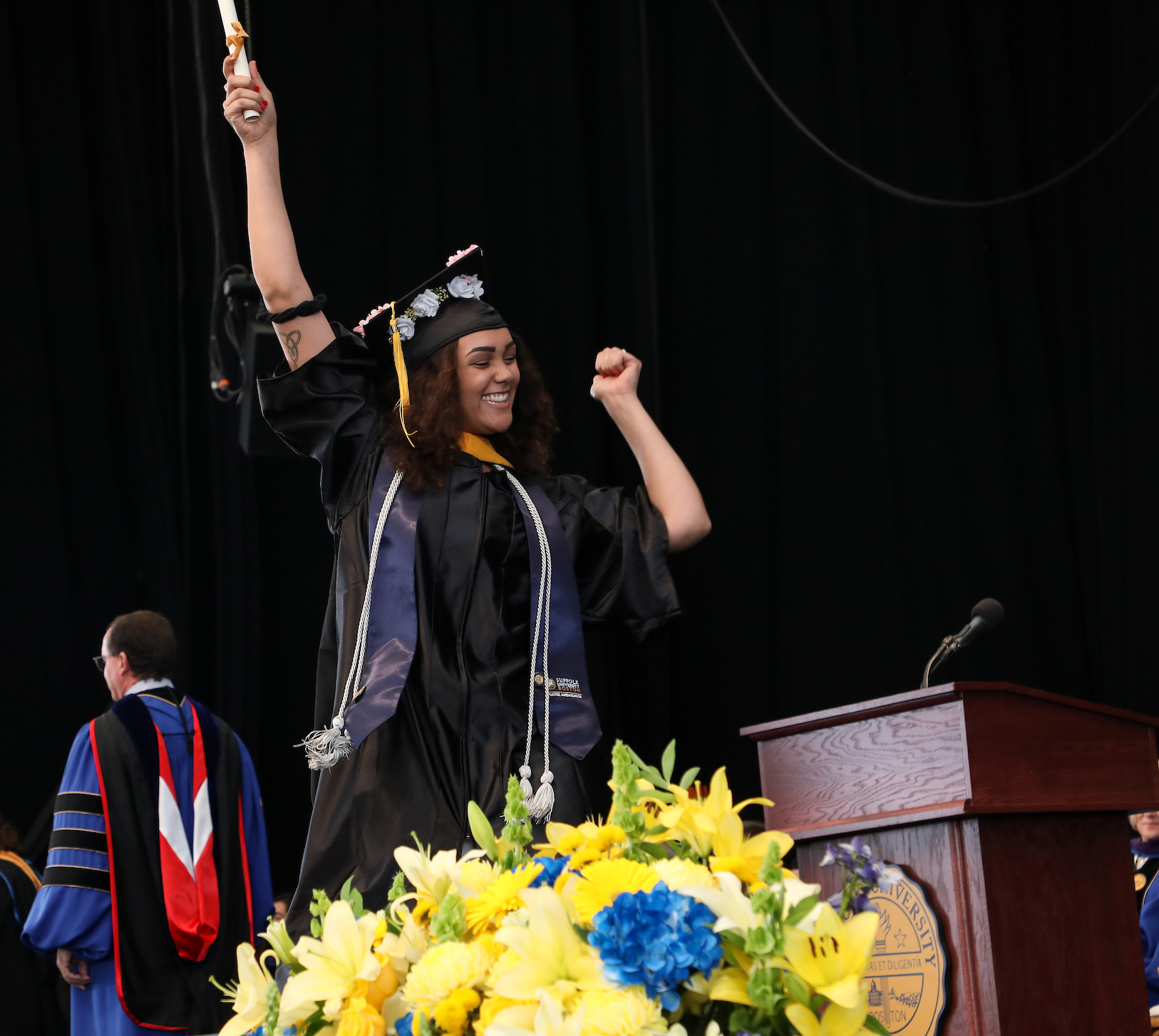 Brenna lifts her scroll high above her head as she crosses the stage at Commencement.