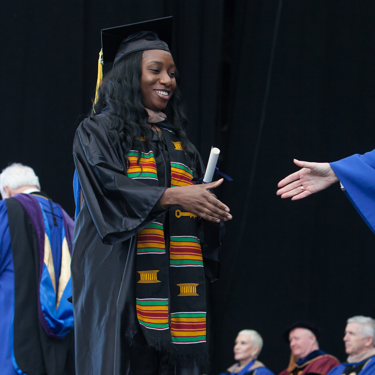 Brittani Cesar preparing to shake an administrator's hand while crossing the stage at Commencement.