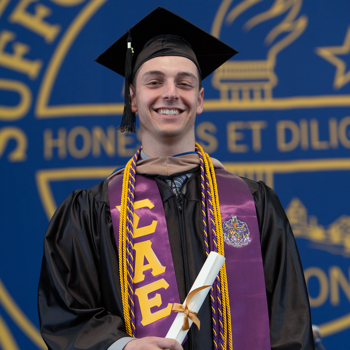 Dan holding up his scroll and smiling for the camera wearing his cap and gown while crossing the stage at Commencement.