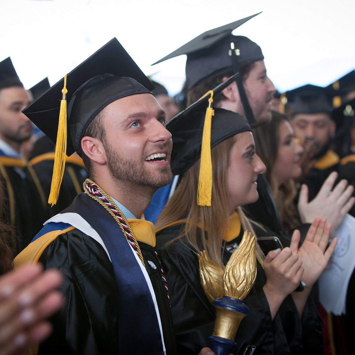 Jonathan holding the Suffolk torch in the crowd wearing his cap and gown during Commencement.