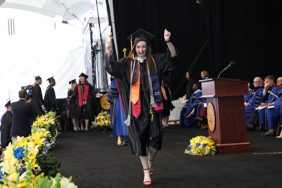 Laurel celebrates, holding her scroll high, as she walks across the stage at Commencement.