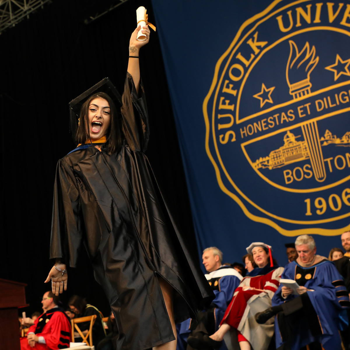 Olivia LeDonne holds up her scroll on stage during Commencement.