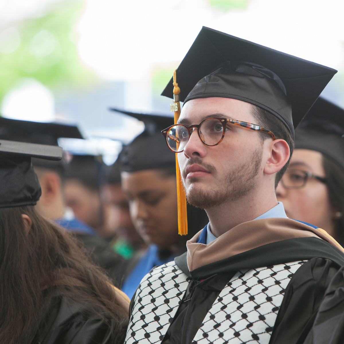 Yazeed Abu-Ghazaleh in his cap and gown sitting in the crowd during Commencement.