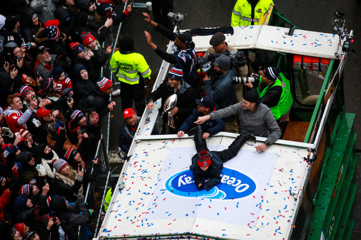 Quarterbacks Tom Brady and Jimmy Garoppolo wave to the crowds from a Duck boat during their victory parade.