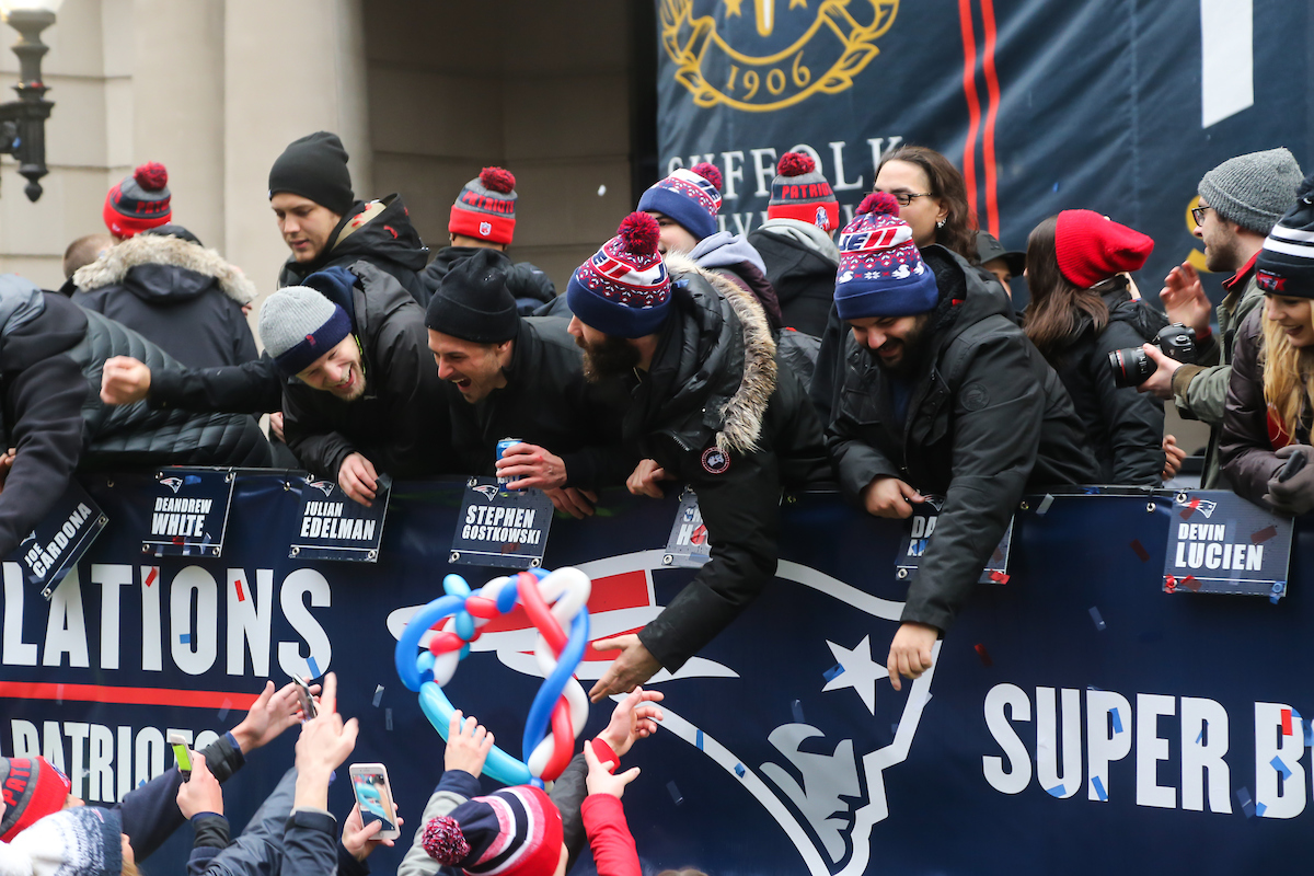 Wide receivers Danny Amendola and Julian Edelman reach out into the crowd of fans during the New England Patriots Super Bowl victory parade in front of Suffolk University's Sargent Hall.