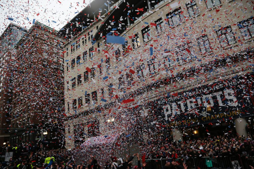 Confetti falls from the sky in front of Suffolk University's Sargent Hall during the New England Patriots Super Bowl victory parade.