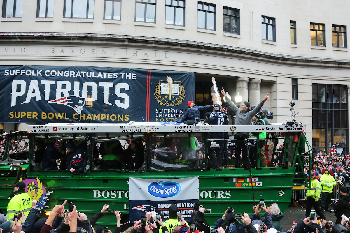Quarterback Tom Brady raises his arms aboard a Duck boat rolling by Suffolk's congratulatory banner outside Sargent Hall.