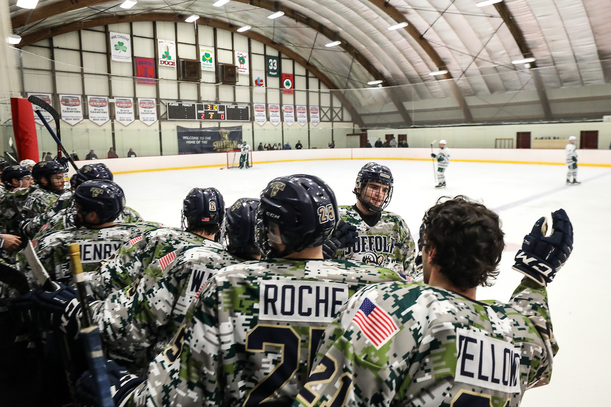 Suffolk player skates by teammates who are wearing camo jerseys.