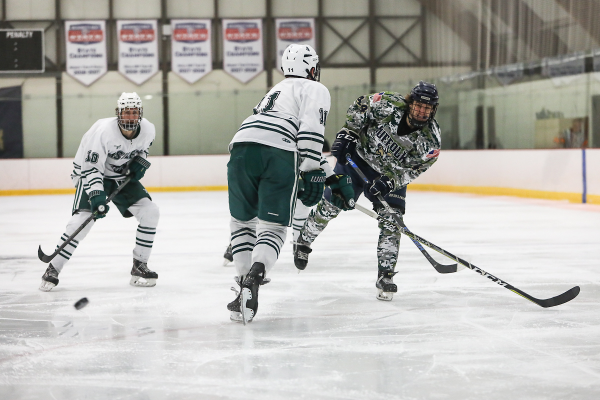 Suffolk player takes a shot from the point during hockey game.