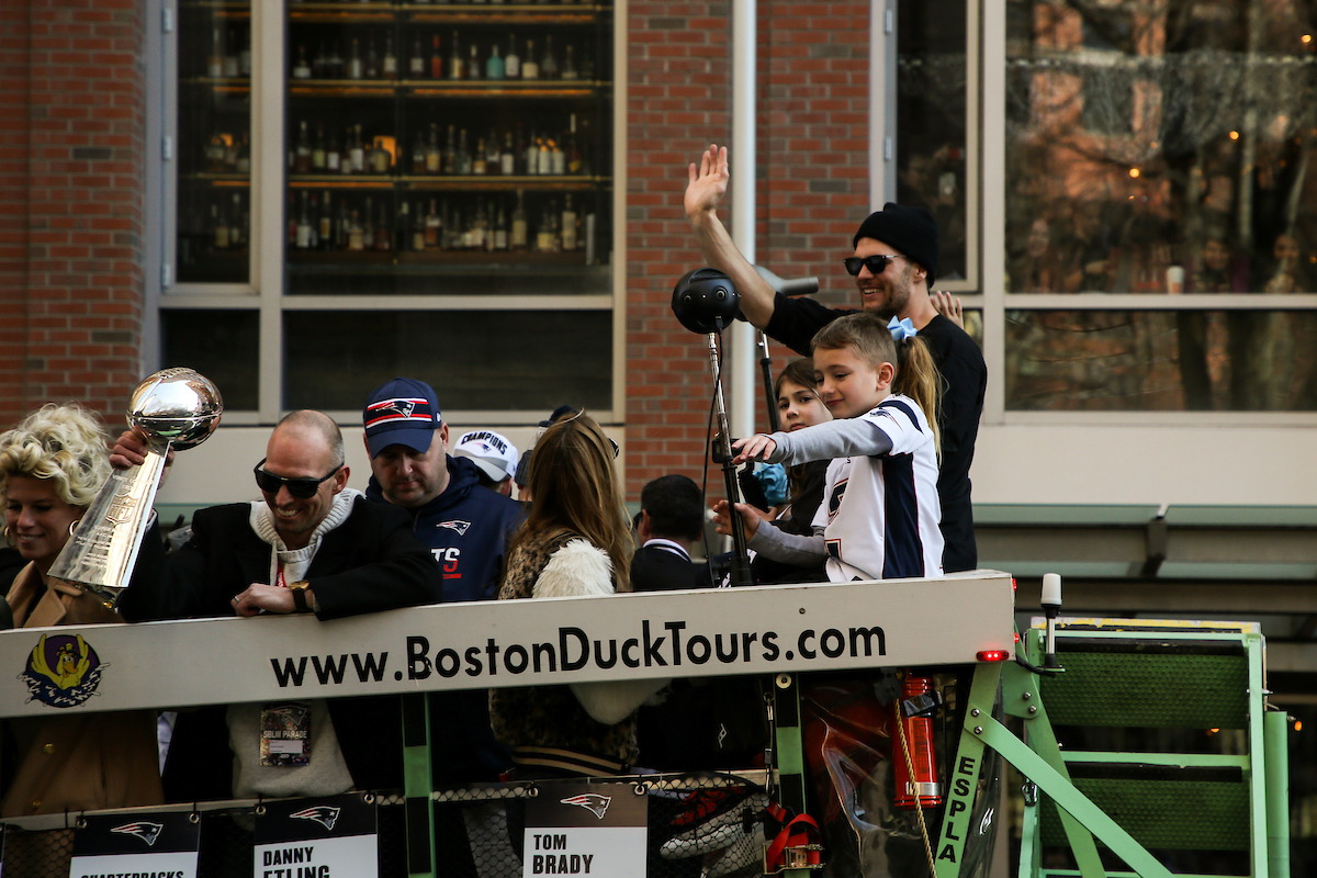 Tom Brady pointing to the crowd at the Patriots Parade in front of Suffolk University.