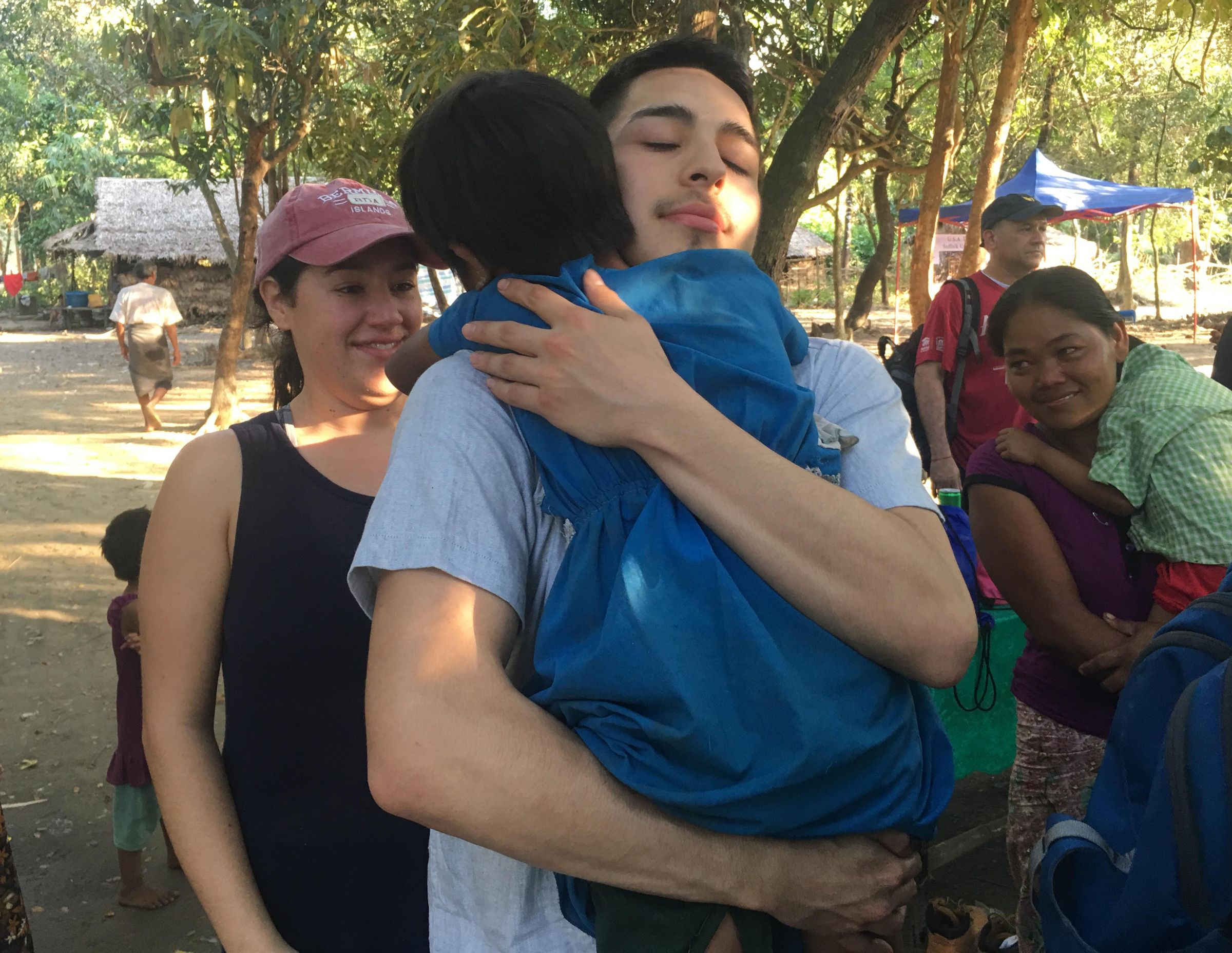 Suffolk student Kevin Luna-Torres holding a child in Myanmar following a week-long home build.