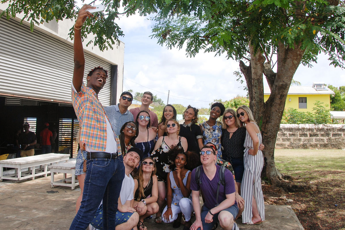 Suffolk Journey students pose for a photo with some of the native people of Barbados during a visit.