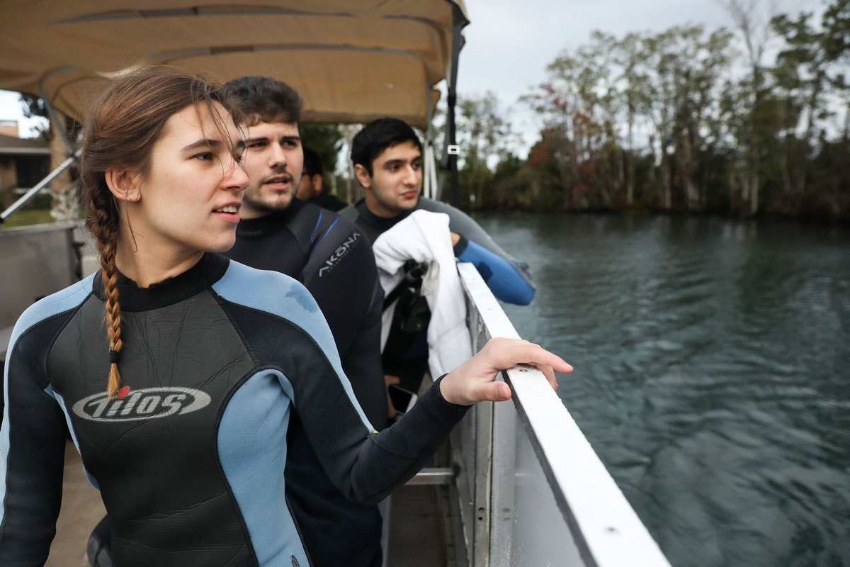 Suffolk Journey students looking out at Crystal River from a boat before swimming with manatees.