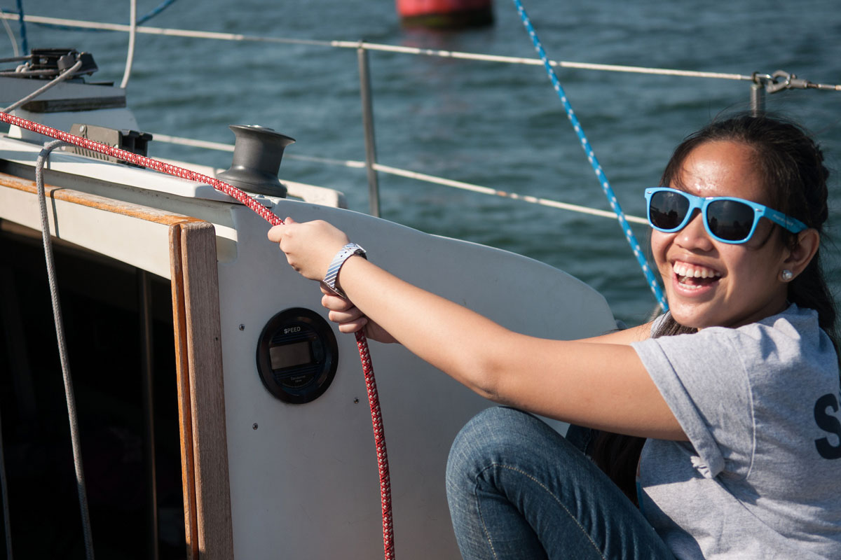 A Suffolk Journey student smiles for the camera as she pulls tight a rope during her sailing lesson.