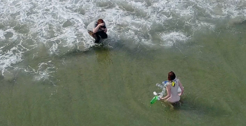 Photographer taking a picture of model on shore line