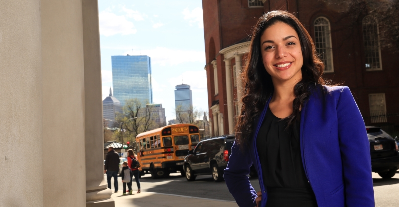 Priscilla Guerrero standing along Tremont Street in front of the law school with the city skyline behind