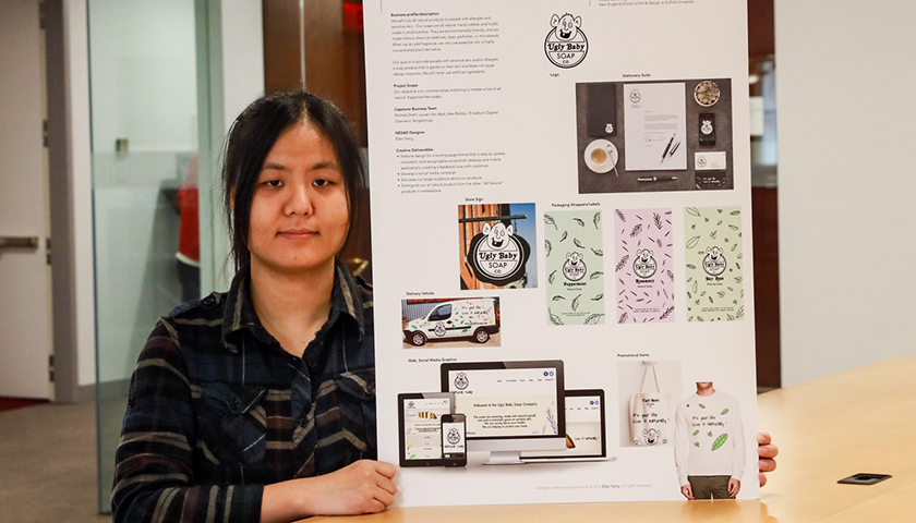Ellen Kang holds a poster showing her design plan for Ugly Baby soap, featuring a drawing of a bald, big-eared baby whose smile shows one tooth
