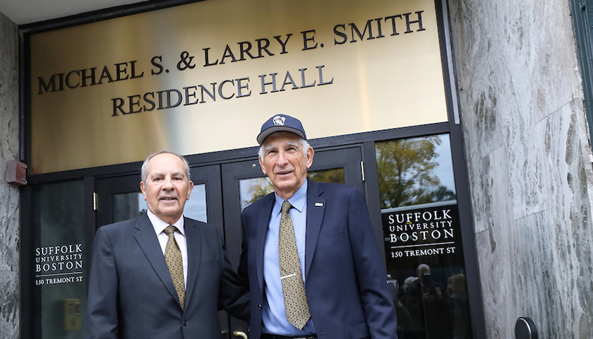 Michael and Larry Smith beneath the residence hall sign bearing their names