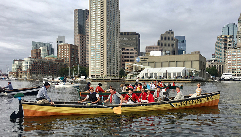 Redcoat reenactors paddle across Boston Harbor in a longboat, with modern skyscrapers providing a backdrop