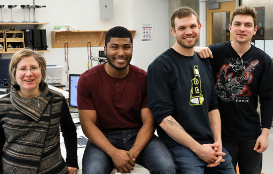 Professor Lisa Shatz in the lab with student teammates Christopher Villar, Justin Bassett, and Roman Deyak, whose solar power project won second place in the Cuba Infrastructure Scholarship Competition