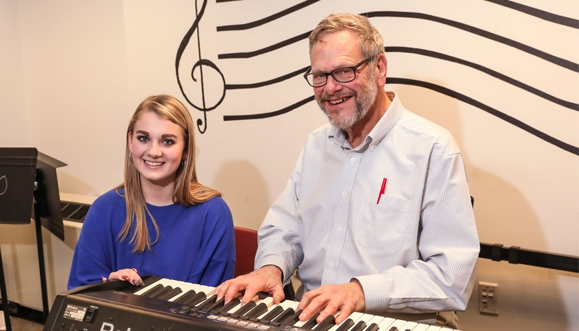 Ryan Coyle sits with Professor R. Harrison Kelton at keyboard