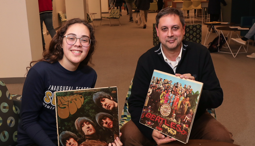 Laurana Quesada holds Rubber Soul LP album cover and David Gallant holds Sargent Pepper LP album cover