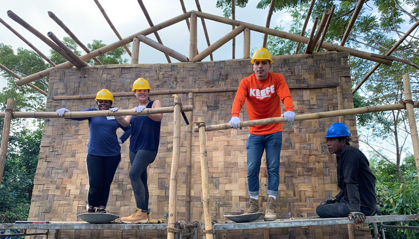 Suffolk students pause while constructing a habitat for humanity home in Myanmar