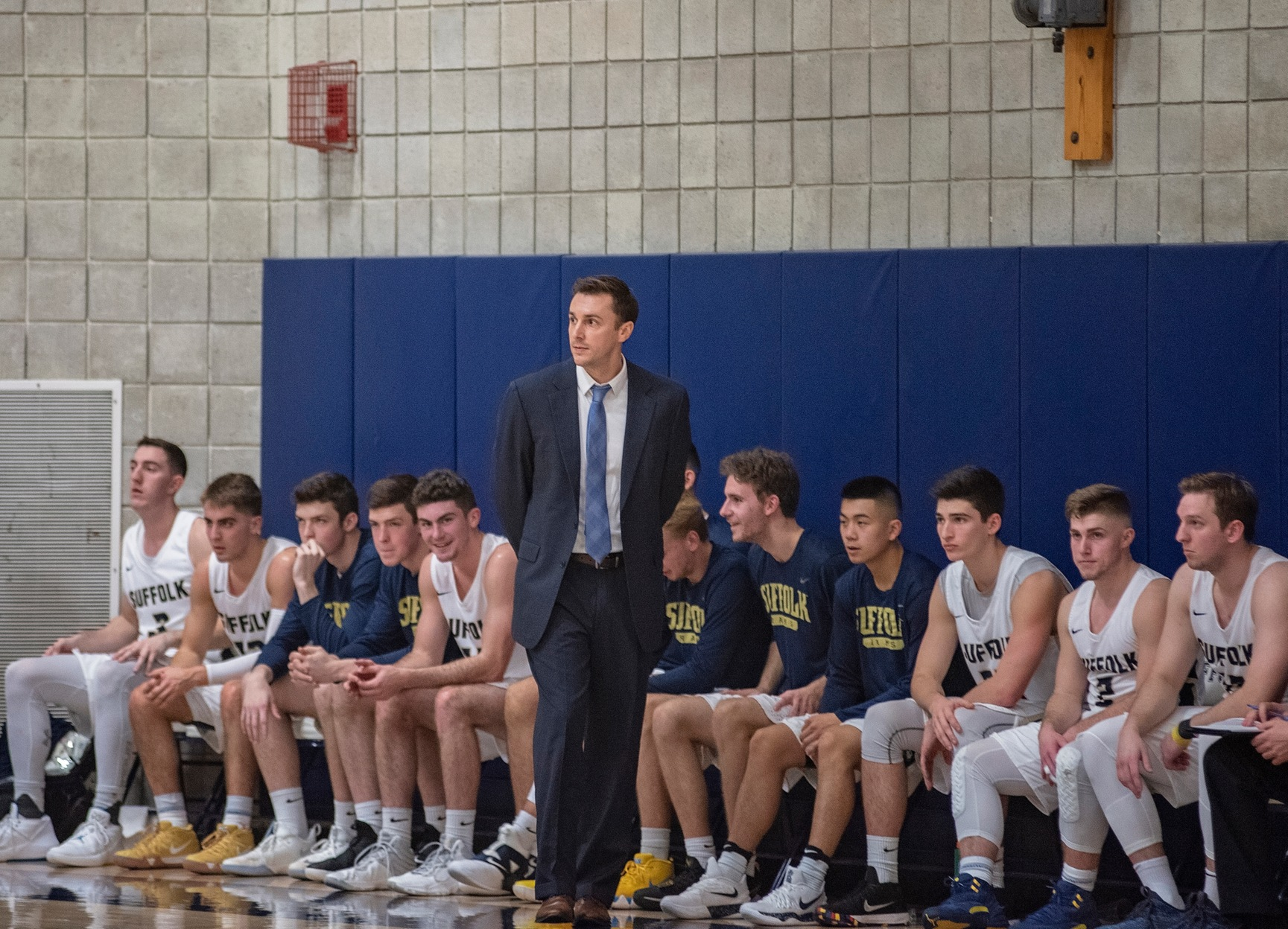 Image of a basketball coach with his players sitting on a bench.
