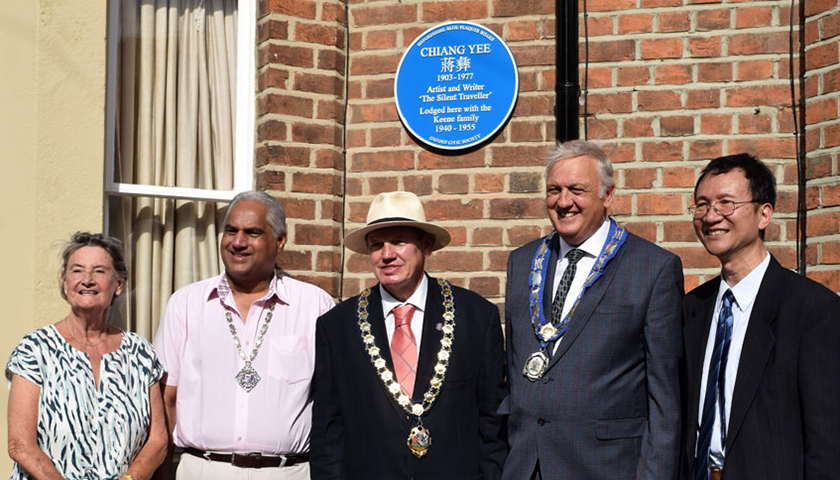 Group of people pose in front of red brick house with blue plaque