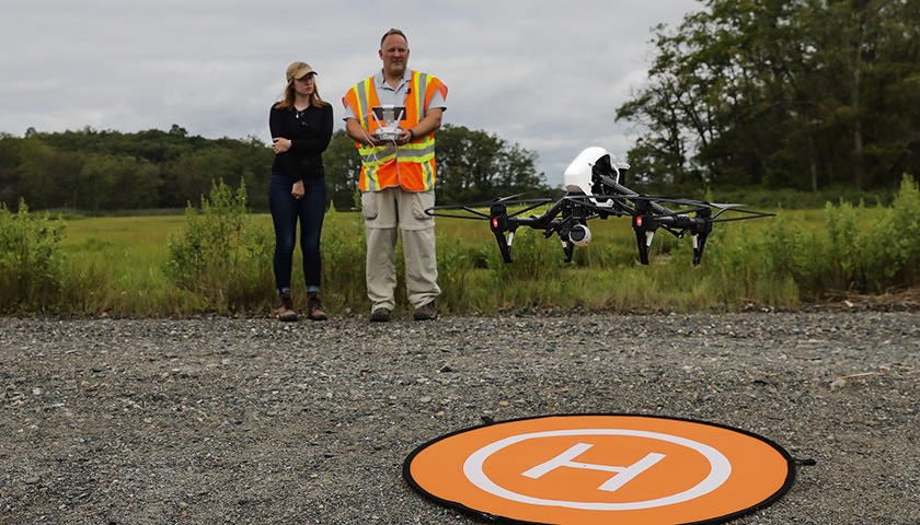 Instructor and student watch as drone takes off from orange launch pad