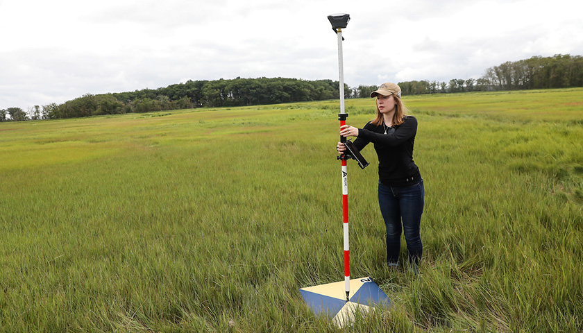 Student holds places pole holding monitoring instrument in center of target to mark geolocation