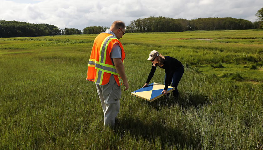 Student bends to set target atop marsh grass as Lussier offers guidance