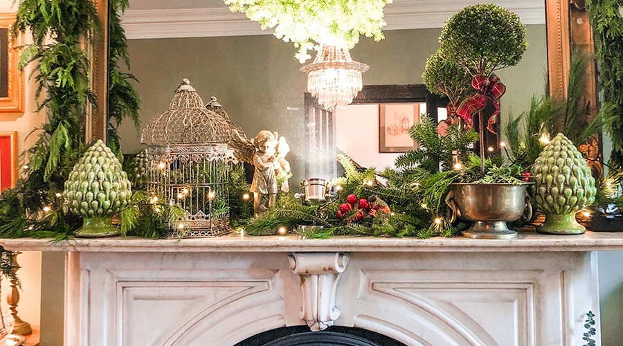 Mantelpiece decorated with greens, a bird cage, angel, topiary and more, all reflected in the mirror over the fireplace