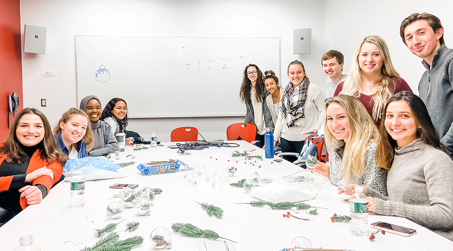 Group of students gathered at a large table making ornaments
