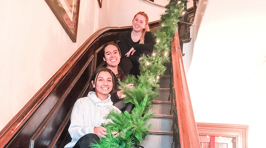 Three women sitting on stairs entwined with a green garland
