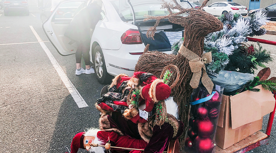 Pile of decorations including grapevine reindeer, elf figures and greens, piled outside a car