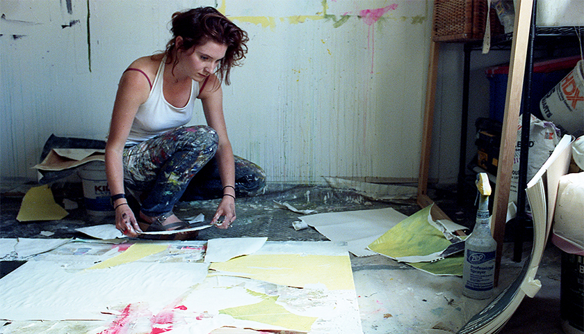 Woman sitting on floor piecing together paste pained paper