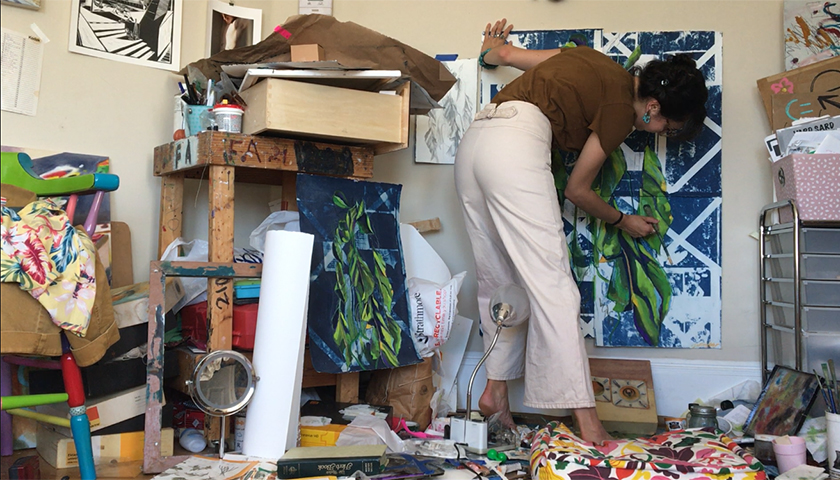 Feltoon painting green leaves over a blue-and-white background in her cluttered bedroom studio