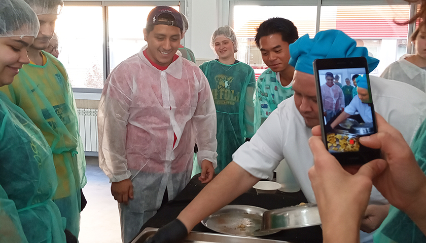 Students in shower caps and smocks help chef prepare food at refuge center