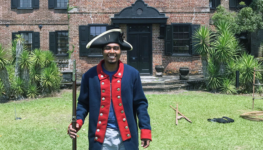Nick Nunez tries on a historical costume outside a Middleton Place building