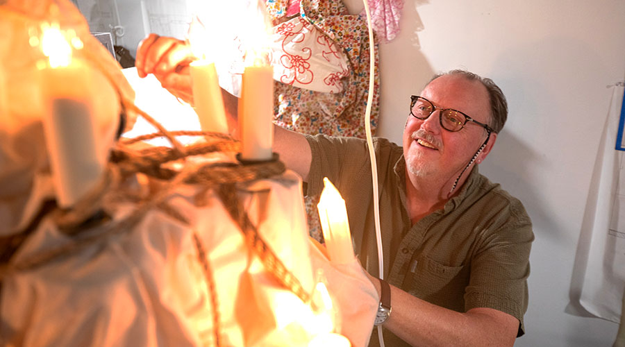 Glow of chandelier lights Richard Chambers' face