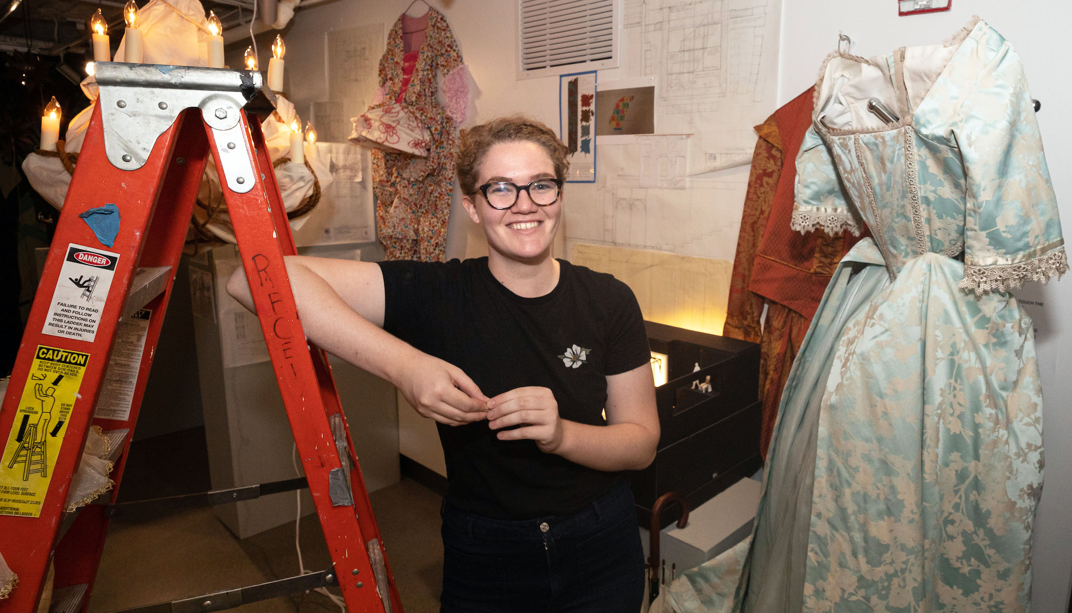 Micaleen Rogers stands with elbow resting on stepladder. Costume hangs on wall on stage right