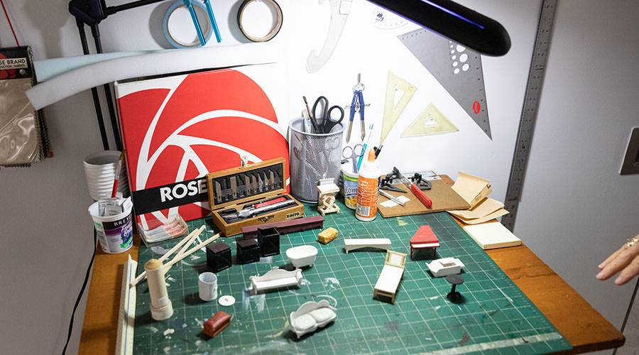 Model of design setup with tiny furniture, rulers, exacto knives, tape and other tools